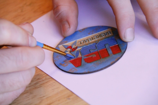 Carefully painting the engraved logo...